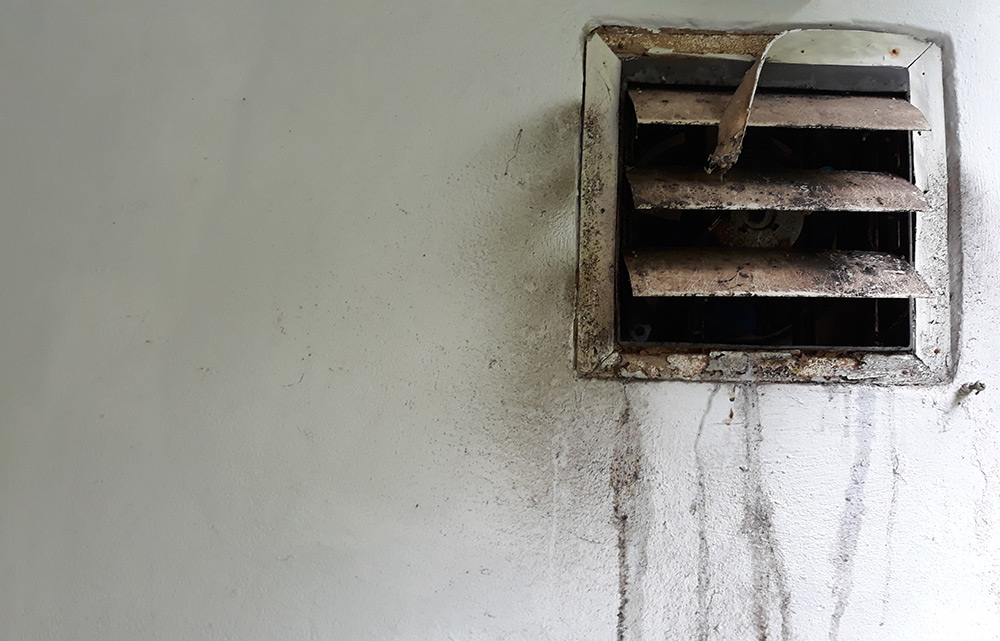 An old vent dripping with mildew