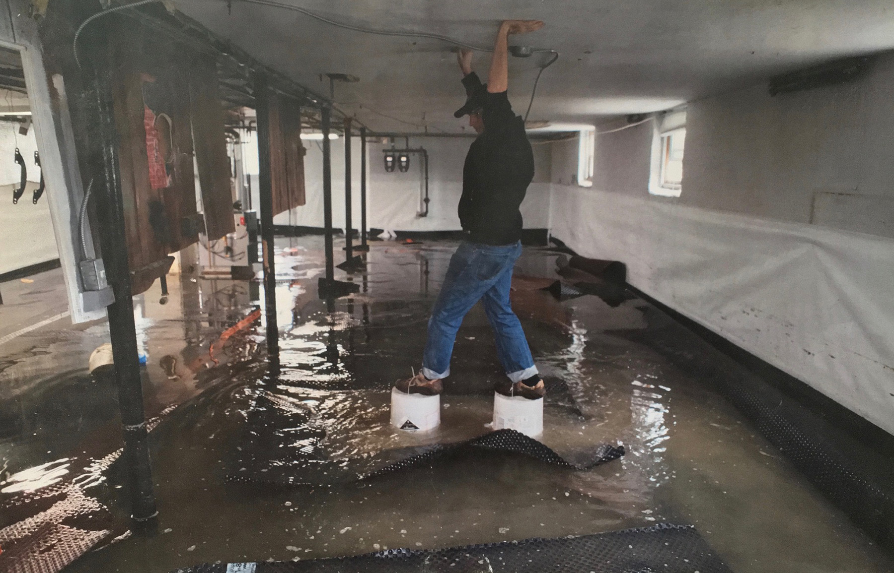 Crawl space technician walking on buckets to avoid severe flooding in residential basement